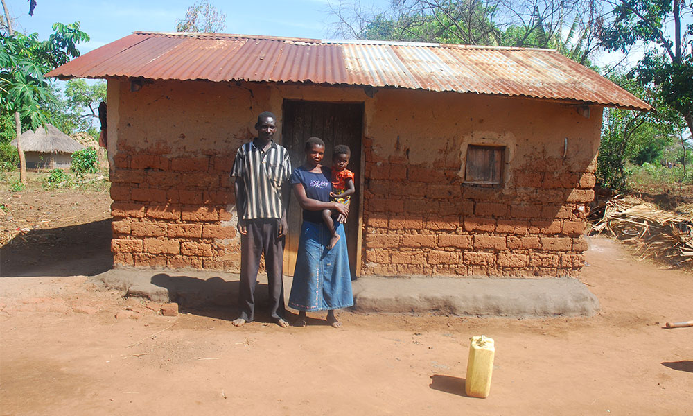 Okello and family infront of their old house
